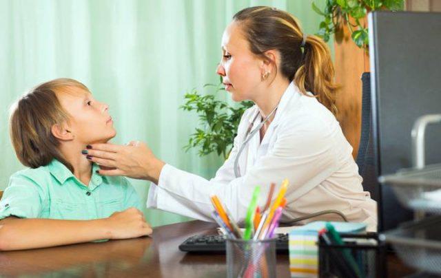 Доктор проверяет рост щитовидной железы у ребенка