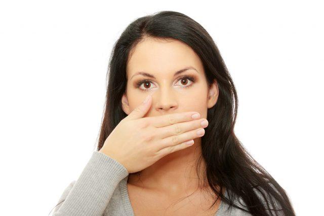 Девушка закрывает рот ладонью