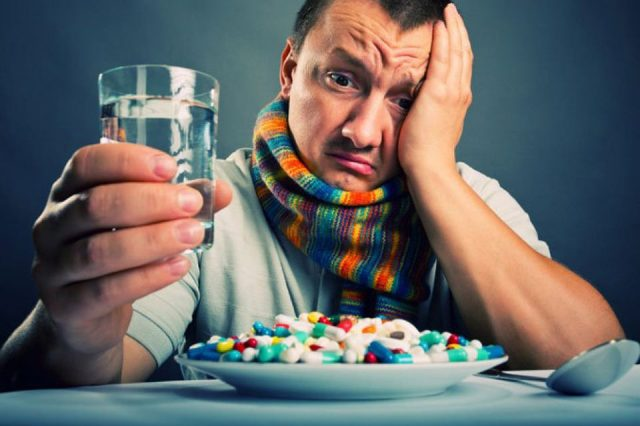 Мужчина со стаканом в руке смотрит на тарелку с таблетками