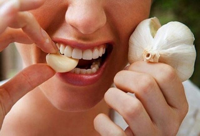 Девушка ест дольку чеснока