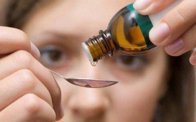 Девушка капает лекарство в ложку