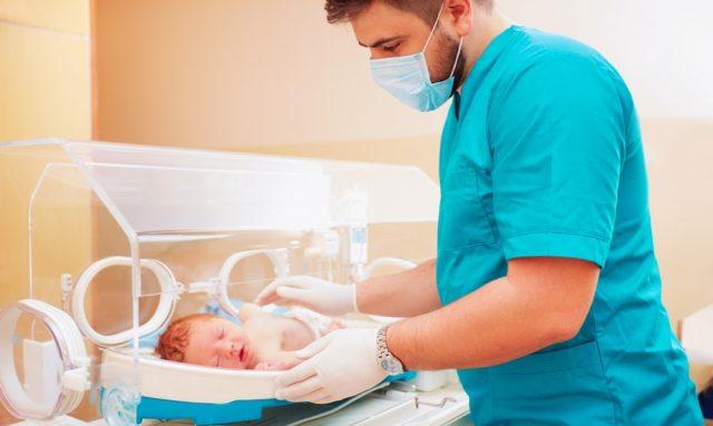 Неонатолог осматривает новорождённого