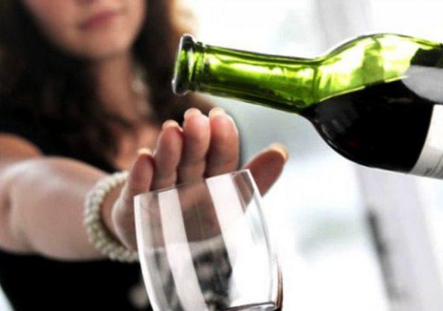 Бутылка с вином, бокал и рука девушки, прикрывающая бокал