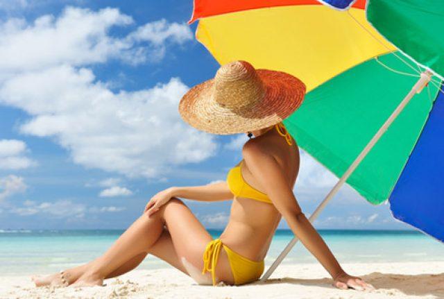 Девушка на пляже под зонтом
