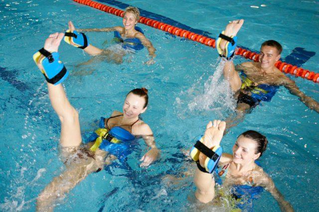 Девушки и парень занимаются аквааэробикой в бассейне