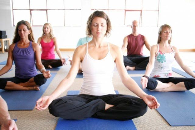 Женщины выполняют йоговские упражнения