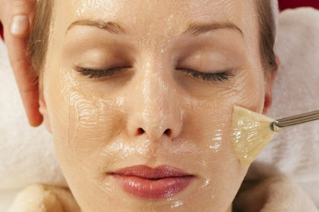 Девушке наносят на лицо маску из желатина