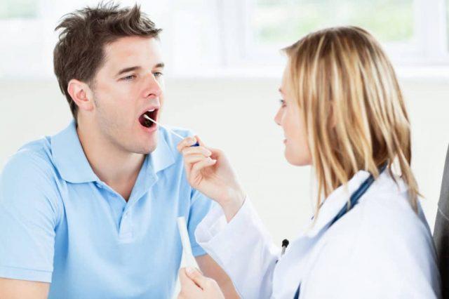 Доктор берёт мазок из ротовой полости пациента