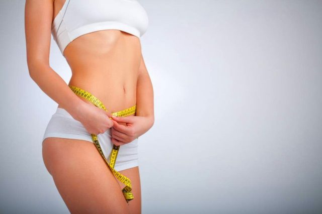 Женщина измеряет объем талии