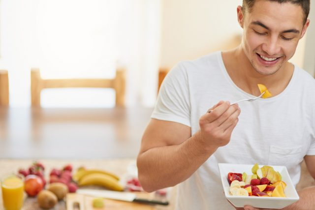 Мужчина ест фрукты