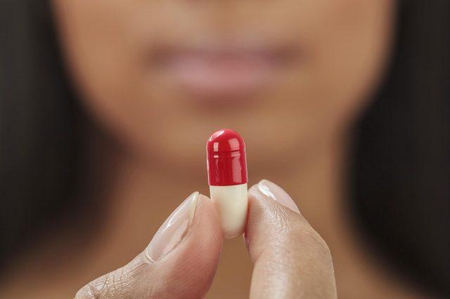Женщина держит таблетку