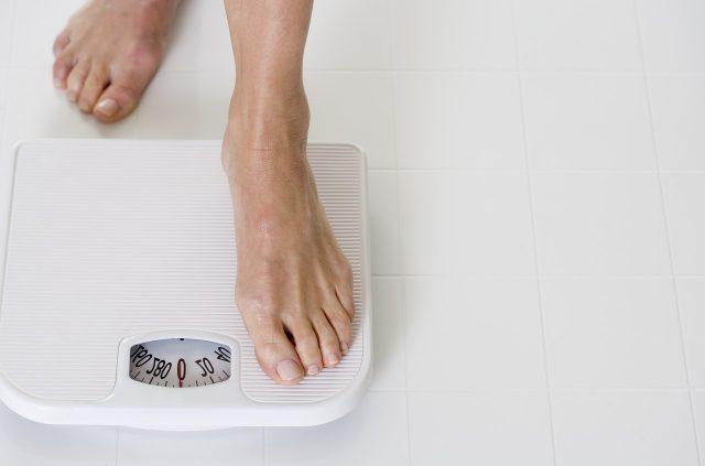 Женщина становится на весы