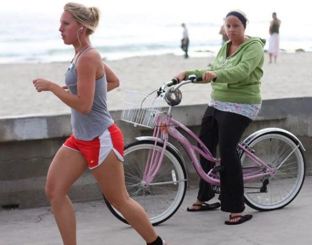 Девушка на велосипеде смотрит на бегующую девушку