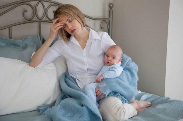Уставшая женщина сидит на кровати и держит младенца