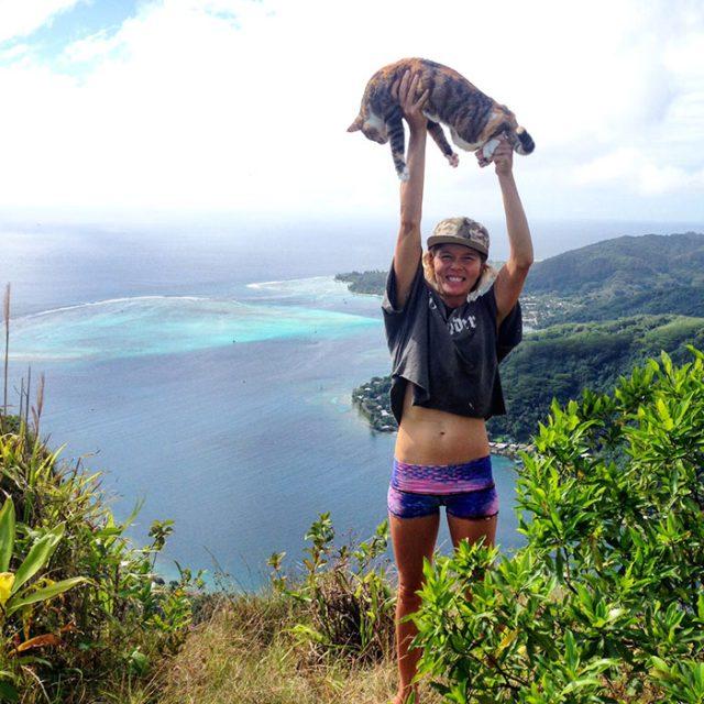 Девушка стоит на склоне холма и держит кошку