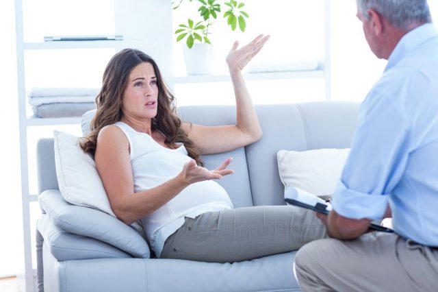 Беременная женщина лежа на диване разговаривает с врачом о проблемах