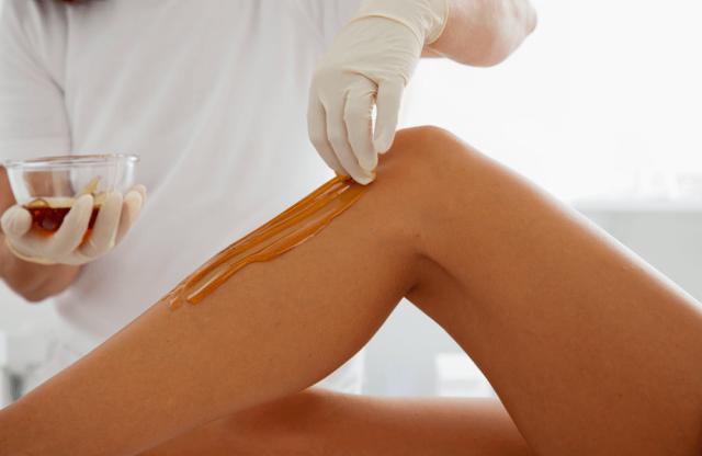 Процедура нанесения сахарной пасты на ногу во время шугаринга