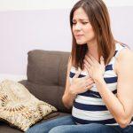 Беременная женщина держится за горло и грудь и морщится