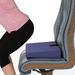 Пямоугольная ортопедическая подушка лежит на кресле