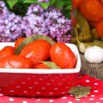 Солёные помидоры в тарелке на красной салфетке