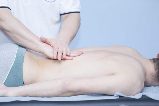 Руки врача в нижней части спины лежачего пациента