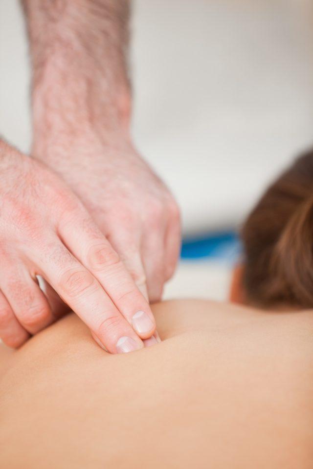 Пальцы врача находятся в нижней части спины лежачего пациента
