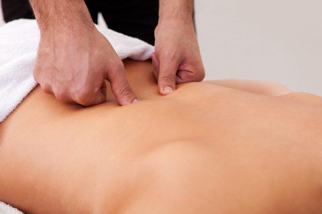 Мужские руки кулаками разминают копчиковую область лежачего пациента