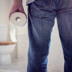 Мужчина в туалете с рулоном туалетной бумаги