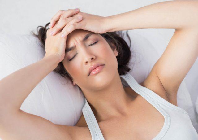 Женщина лежит и держится за голову