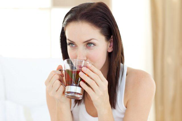 Женщина пьёт травяной чай в прозрачной кружке