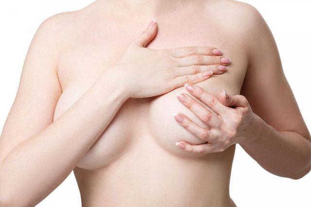Женщина исследует грудь на предмет уплотнений