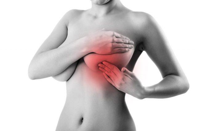 Женщина ощупывает грудь
