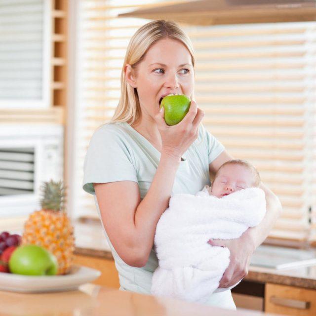 Женщина с ребёнка кусает яблоко