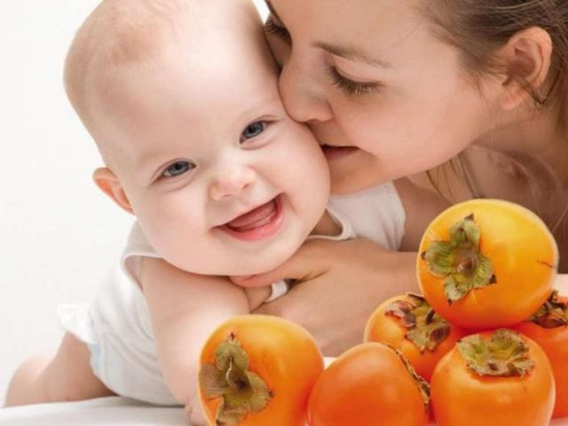 Мама целует малыша, а перед ними на столе лежит хурма