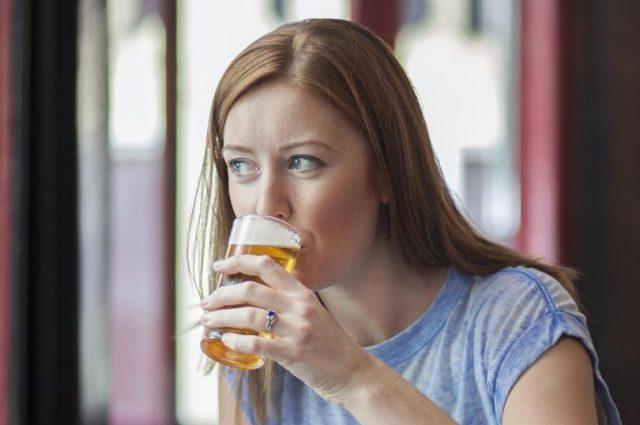 Женщина пьёт пиво
