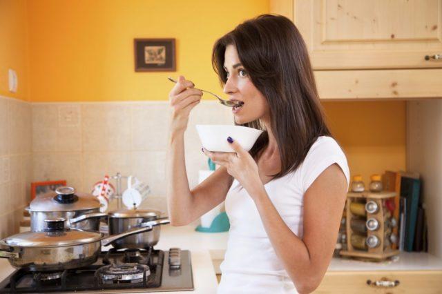 Женщина пробует суп