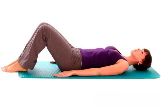 жнщина лежит на коврике для йоги