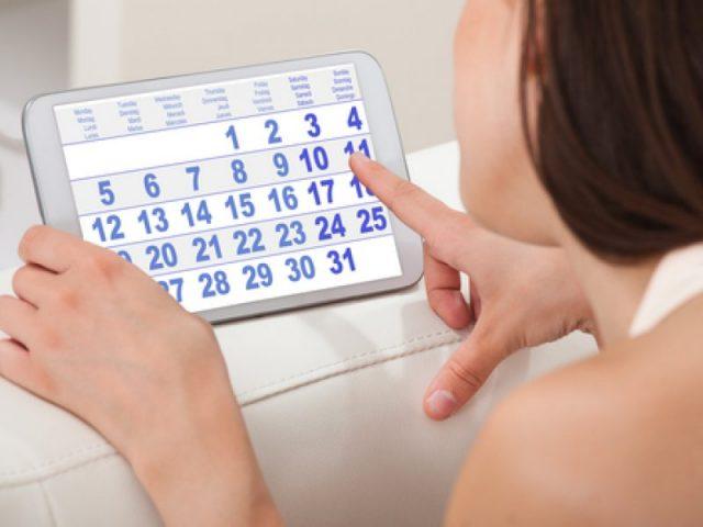 Девушка смотрит в календарь на планшете