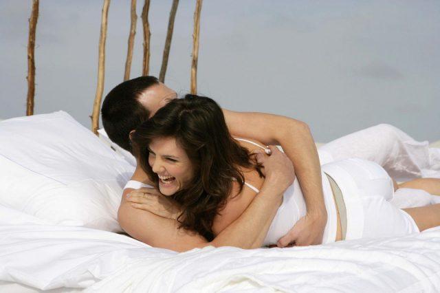 Девушка смеётся, обнявшись с парнем в постели