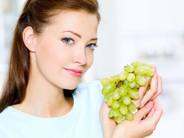 Женщина держит в руке виноградную гроздь