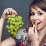 Женщина ест зелёный виноград