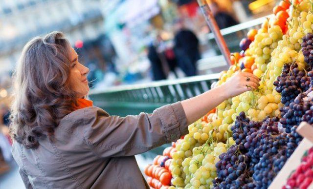 Женщина выбирает виноград на рынке