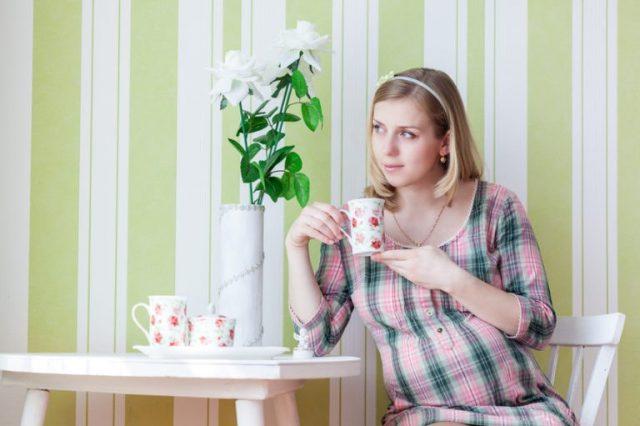 Беременная женщина пьёт чай