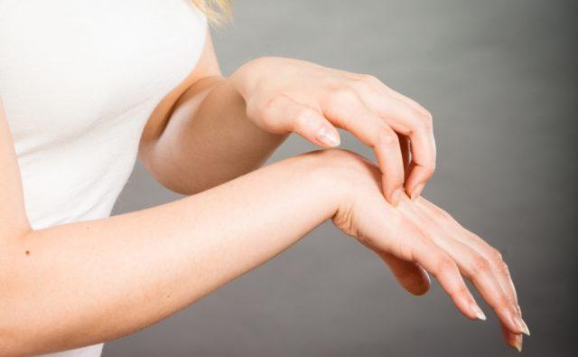 Женщина чешет зудящую руку