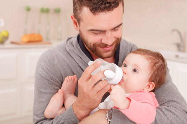 папа кормит малыша смесью