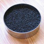 Гранулы активированного угля в железной круглой миске на столе