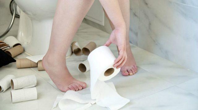 Человек в туалете и рулоны туалетной бумаги на полу