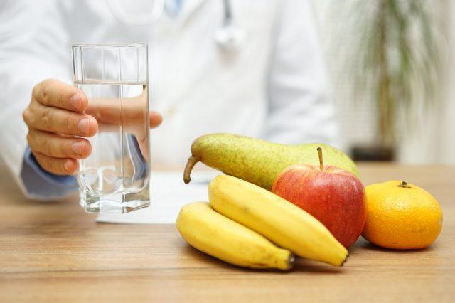 Стакан воды в руке у человека и фрукты на столе