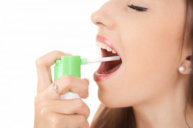 женщина прыскает спрей в рот