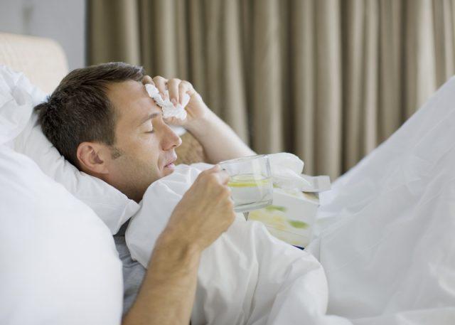 Больной мужчина лежит в постели